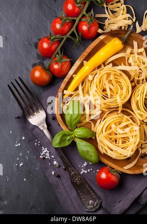 Tagliatelle con peperoncino, pomodori e basilico Foto Stock