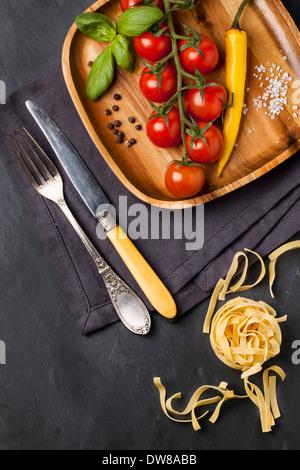 Pomodori in vigna, basilico e peperoncino giallo servite sul piatto di legno Foto Stock