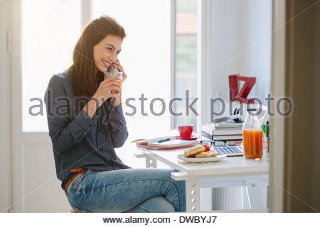 Giovane donna con il telefono mentre breakfasting Foto Stock