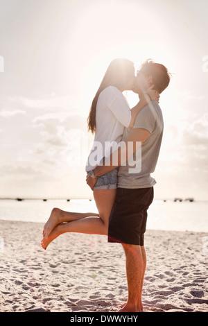Colpo di profilo di coppia giovane baciare sulla spiaggia Foto Stock