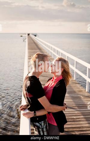 Profilo shot coppia romantica sfregamento dei nasi sul molo Foto Stock