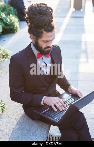 Elegante Elegante dreadlocks imprenditore utilizzando notebook nel panorama aziendale Foto Stock