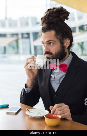 Elegante Elegante dreadlocks imprenditore presso il bar nel panorama aziendale Foto Stock