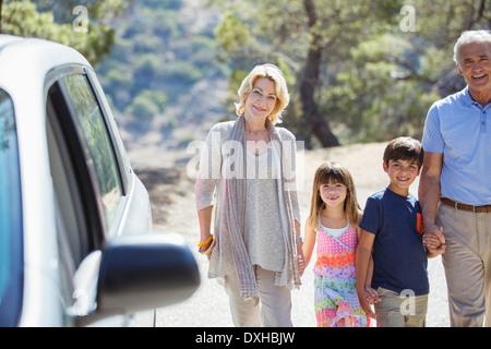 Nonni e nipoti holding hands fuori dall'auto Foto Stock