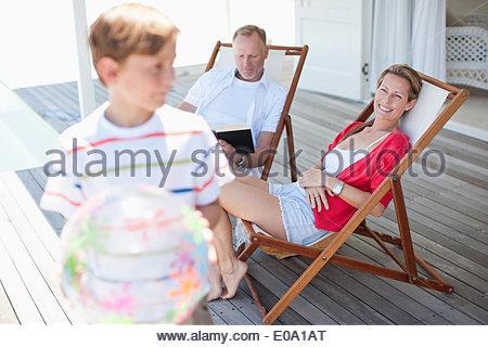 I genitori a guardare il figlio gioca con la palla sul ponte Foto Stock