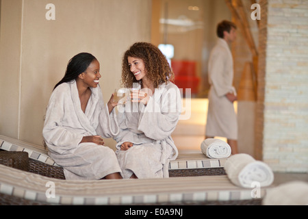 Due giovani donne in chat sui lettini a spa Foto Stock