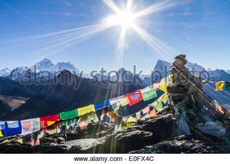 Il sole si libra sopra una roccia Cairn adornata con bandiere di preghiera con il Monte Everest in background, Gokyo Foto Stock