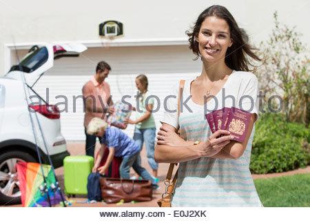 Ritratto di donna sorridente tenendo i passaporti in viale con famiglia macchina impacchettatrice in background Foto Stock