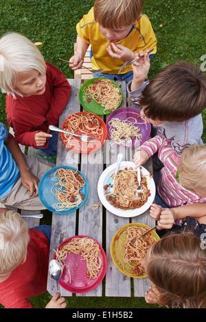 Vista aerea di sette bambini mangiare spaghetti al tavolo da picnic Foto Stock