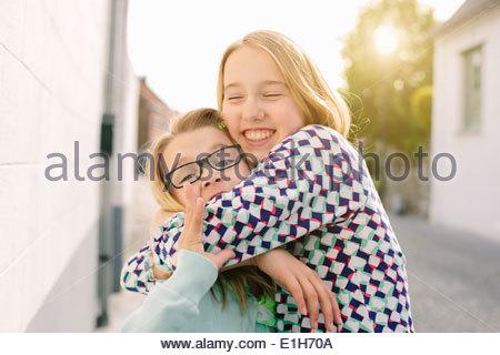 Due sorelle abbracciando con entusiasmo Foto Stock