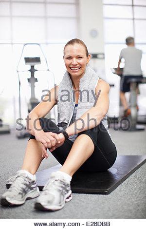 Ritratto di donna sorridente seduto sul tappeto di esercizio in palestra Foto Stock