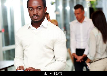 Ritratto di un imprenditore utilizza lo smartphone e guardando la telecamera di fronte ai colleghi Foto Stock