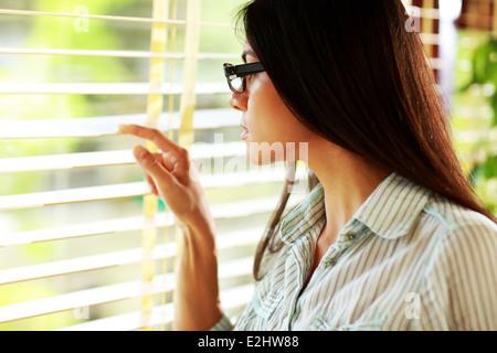 Imprenditrice in bicchieri cercando nella finestra di office Foto Stock