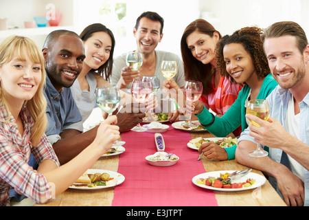 Gruppo di amici seduti attorno al tavolo con Cena Foto Stock