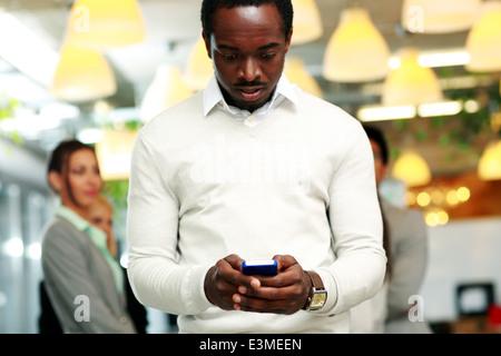 Sorpreso imprenditore utilizza lo smartphone di fronte ai colleghi Foto Stock