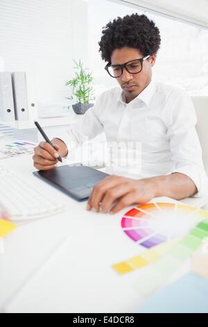 Hipster designer che lavora presso la sua scrivania Foto Stock