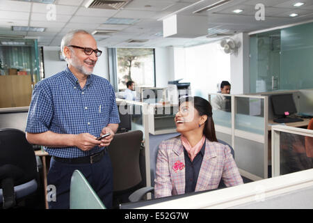 Senior l uomo e la donna avente una chat in ufficio Foto Stock