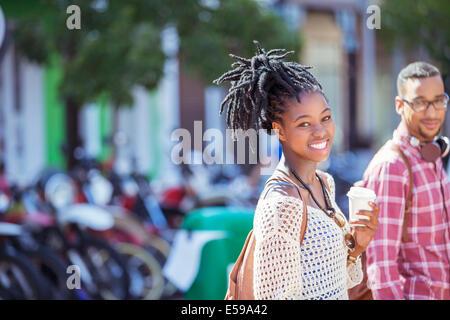 Donna di bere il caffè sulla strada di città Foto Stock