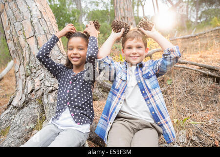 Bambini che giocano con i coni di pino in foresta Foto Stock