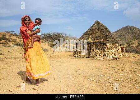 Madre con suo figlio nella parte anteriore di una capanna tradizionale nelle Highlands di Eritrea, Africa Foto Stock