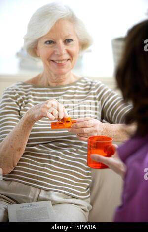 Home aiuto assistendo donna anziana per la somministrazione dei farmaci. Foto Stock