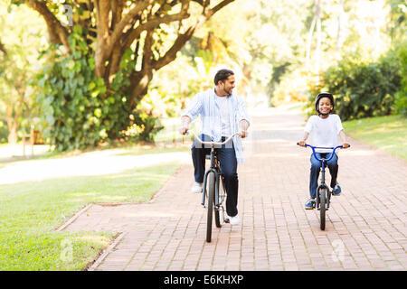 Allegro indiano padre e figlia riding bike nel parco Foto Stock