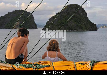 I bambini sulla barca a vela nella Baia di Halong, Vietnam, sud-est asiatico - al crepuscolo in vacanza Foto Stock
