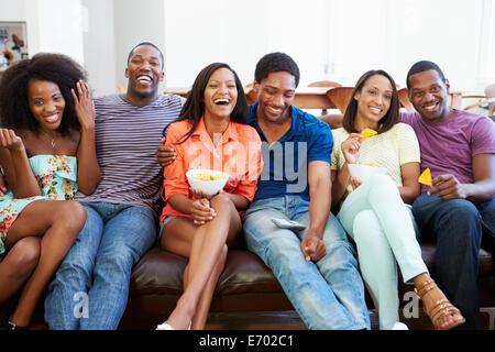 Gruppo di amici seduti sul divano guardando la TV insieme Foto Stock