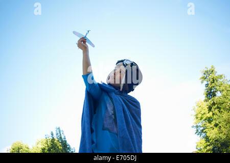 Giovane ragazzo in costume, giocando con aeroplano giocattolo Foto Stock