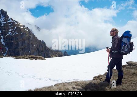 Uomo maturo in piedi nella neve, montagne di Bucegi, Transilvania, Romania Foto Stock