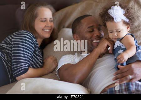 La madre e il padre sdraiato sul letto con la nostra bambina Foto Stock