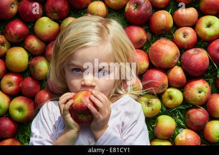 Ritratto di bambino biondo giovane ragazza distesa e mangiare sul prato con mele sfondo, giace Foto Stock