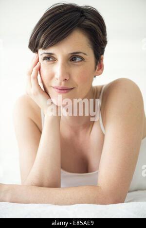 Donna sdraiata sul letto, ritratto Foto Stock