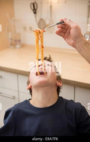 Padre figlio di alimentazione con gli spaghetti Foto Stock