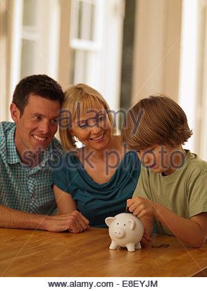 I genitori guardare figlio mettendo moneta nel salvadanaio Foto Stock