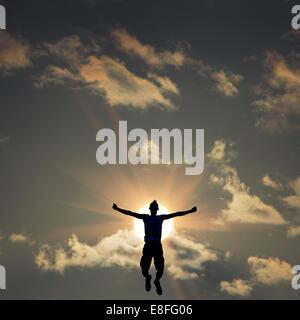Silhouette di uomo jumping davanti al sole Foto Stock