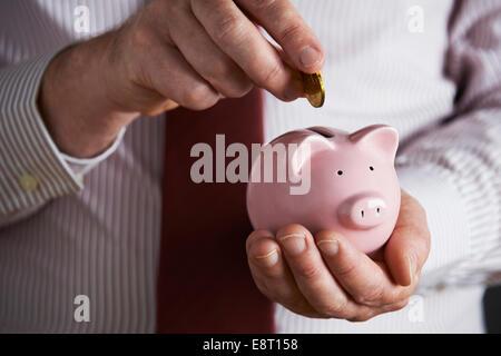 Imprenditore mettendo moneta nel salvadanaio Foto Stock