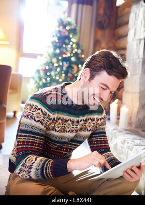 Uomo con tavoletta digitale in log cabin Foto Stock
