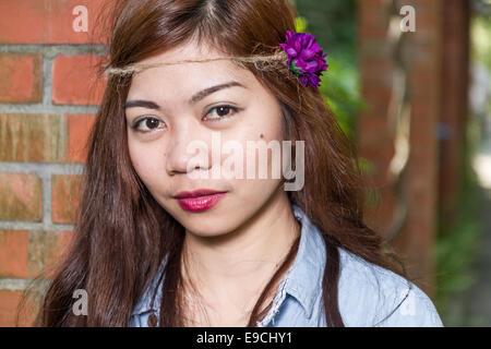 Pinoy donna in un giardino verde in agriturismo, appoggiata contro il pilastro di mattoni Foto Stock