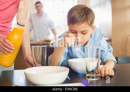 Sezione mediana della donna con bottiglia di succo di frutta in piedi dal figlio avente la colazione con uomo sullo Foto Stock
