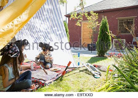 Fratelli e sorelle la riproduzione di pirati in backyard fort Foto Stock