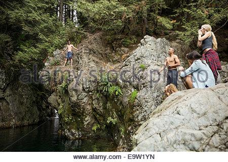 Ragazzo preparando per passare dalle rocce in acqua Foto Stock
