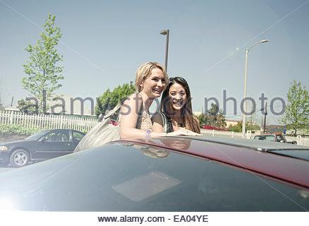 Due donne, ridere, in piedi accanto a AUTO Foto Stock