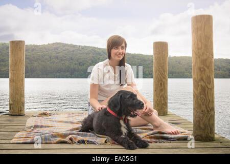 Giovane donna seduta con pet terrier alla fine di un pontile sul lago Foto Stock