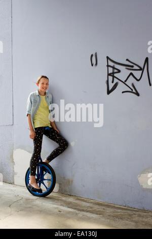 Ragazza adolescente sul monociclo, ritratto Foto Stock