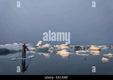 Uomo su paddleboard, Jokulsarlon laguna glaciale, Skaftafell National Park, Islanda Foto Stock