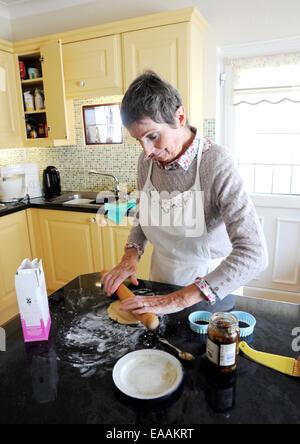 Donna anziana pensionata Cottura torte di carne macinata a casa nella sua cucina per Natale Foto Stock