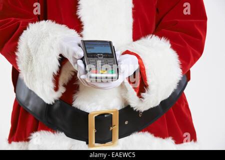 Close Up di Santa Claus tenendo il lettore di carte di credito Foto Stock