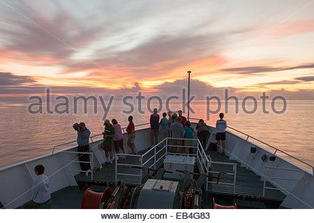 I passeggeri a bordo di un turismo Expedition nave Godetevi il tramonto in rotta verso le Isole Galapagos. Foto Stock