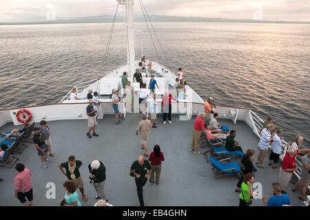 I passeggeri a bordo di un turista Expedition nave Godetevi il tramonto nelle isole Galapagos. Foto Stock